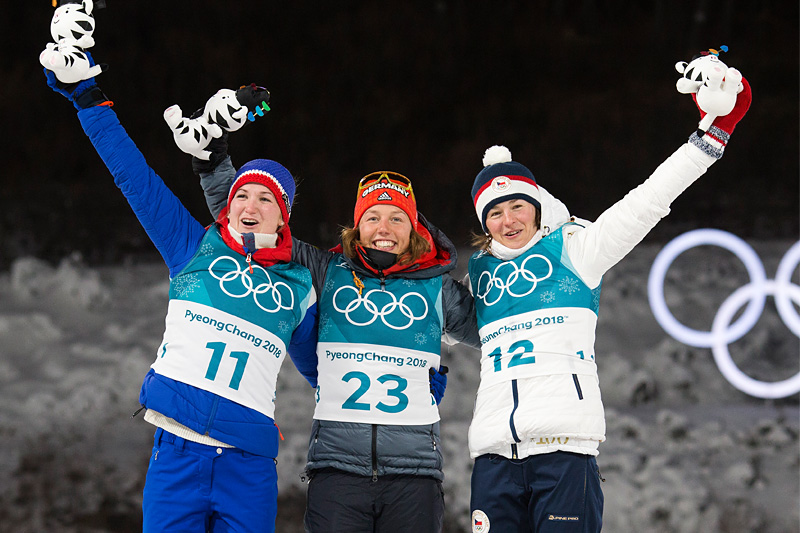 Seierspallen i kvinnenes sprint i skiskyting under OL Pyeongchang 2018. Fra venstre: Marte Olsbu (sølv), Laura Dahlmeier (gull), Veronika Vitkova (bronse). Foto: Manzoni/NordicFocus.
