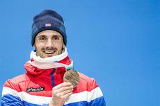 Hans Christer Holund viser frem sin OL-bronse fra 30 km skiathlon fra Pyeongchang 2018. Foto: Modica/NordicFocus.