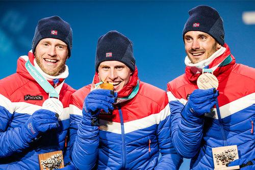 Seierspallen etter 30 km skiathlon under OL Pyeongchang 2018. Fra venstre: Martin Johnsrud Sundby (sølv), Simen Hegstad Krüger (gull) og Hans Christer Holund (bronse). Foto: Modica/NordicFocus.