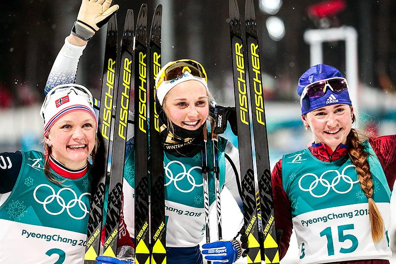 Seierspallen etter damenes OL-sprint i Pyeongchang 2018. Fra venstre: Maiken Caspersen Falla (2.-plass), Stina Nilsson (1) og Yulia Belorukova (3). Foto: Modica/NordicFocus.