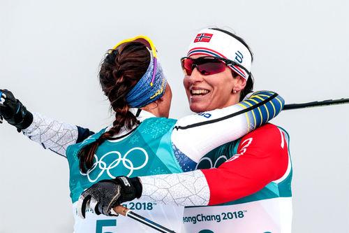 Marit Bjørgen gir seiersklem til Charlotte Kalla etter 15 km skiathlon i Pyeongchang-OL 2018. Selv ble Marit nummer 2. Foto: Modica/NordicFocus.