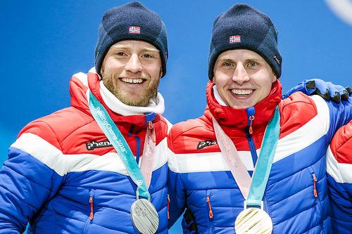 Martin Johnsrud Sundby og Simen Hegstad Krüger med sølv og gull fra skiathlon under OL i Pyeongchang 2018. Sundby går onsdagen lagsprint med Johannes Høsflot Klæbo, mens Krüger er sendt hjem. Foto: Modica/NordicFocus.