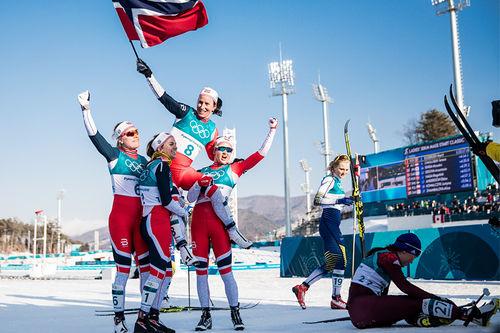 Marit Bjørgen holdes på gullstol av Ragnhild Haga, Heidi Weng og Ingvild Flugstad Østberg etter OL-gull i Pyeongchang 2018. Nå er hun ute av laget, men de øvrige er med og er del av den gode grunnstammen i norsk langrenn. Foto: Modica/NordicFocus.