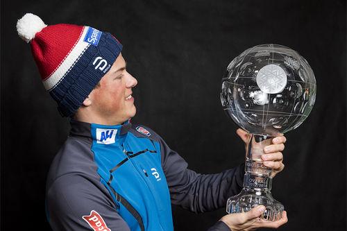 Johannes Høsflot Klæbo medt troféet som viser at han var vinner av verdenscupen sammenlagt i sesongen 2017/2018. Foto: Modica/NordicFocus.