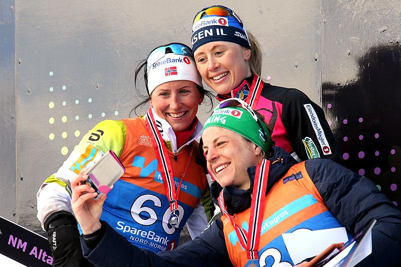 Seierspallen etter damenes 30 km fri teknikk under NM i Alta 2018. Fra venstre: Marit Bjørgen (2.-plass), Ragnhild Haga (1) og Astrid Uhrenholdt Jacobsen (3). Foto: Erik Borg.