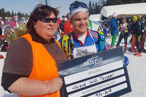 Håvard Solås Taugbøl med premiepengene gitt av Mosetertoppen Skiline for sin seier i Lillehammer Troll Ski Marathon, utdeler er rennleder Turi Elise Kaus. Arrangørfoto.