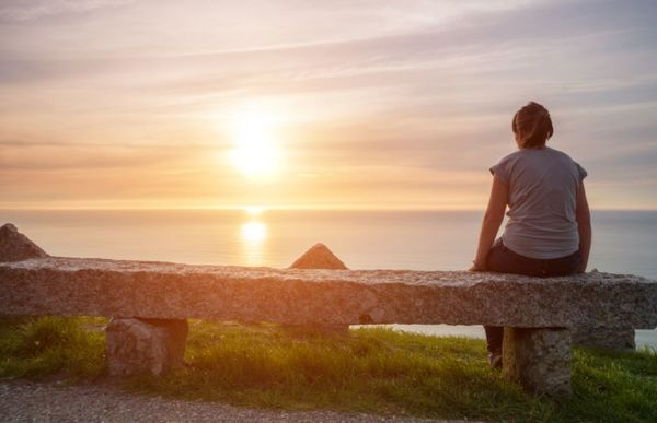 Jente som ser på solnedgangen