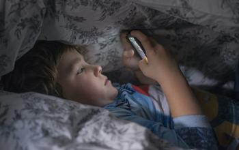 Barn med telefon i sengen