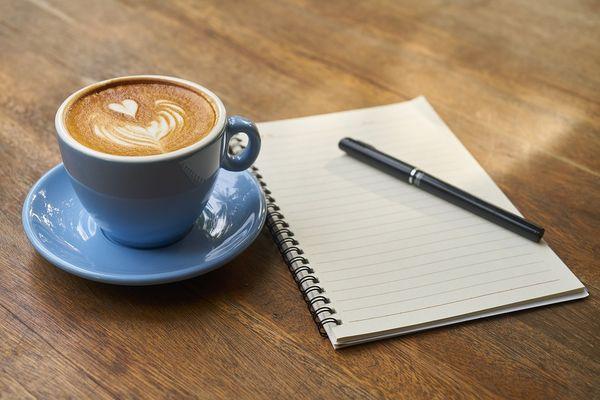 Kaffekopp og skriveblokk