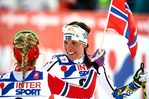 Gullvinner Therese Johaug tar imot bronsevinner Charlotte Kalla på den 30 km lange fellesstarten med skibytte under VM i Falun 2015. Foto: NordicFocus.