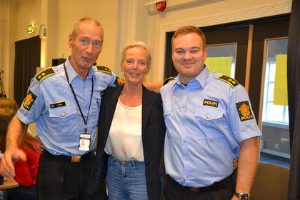Kjersti Falck flankert av politimenn På tvers