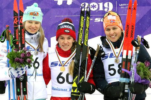 Seierspallen etter damenes 10 km fri under U23-VM i Lahti 2019. Fra venstre: Eveliina Piippo (2.-plass), Mariya Istomina (1) og Tiril Udnes Weng (3). Foto: Erik Borg.