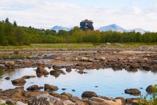 Tursti ved havet med utsikt mot Hamsunsenteret og fjell