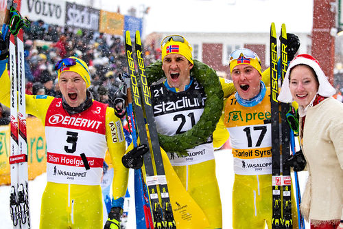 Den norske topptrioen i Vasaloppet 2019, alle fra Team Koteng. Fra venstre: Stian Hoelgaard (2. plass), Tore Bjørseth Berdal (1), Torleif Syrstad (3) og kranskullan. Foto: Manzoni/NordicFocus.
