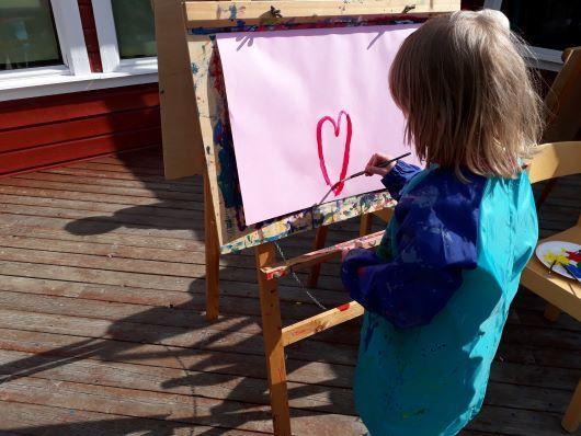 Barn som maler hjerte utendørs