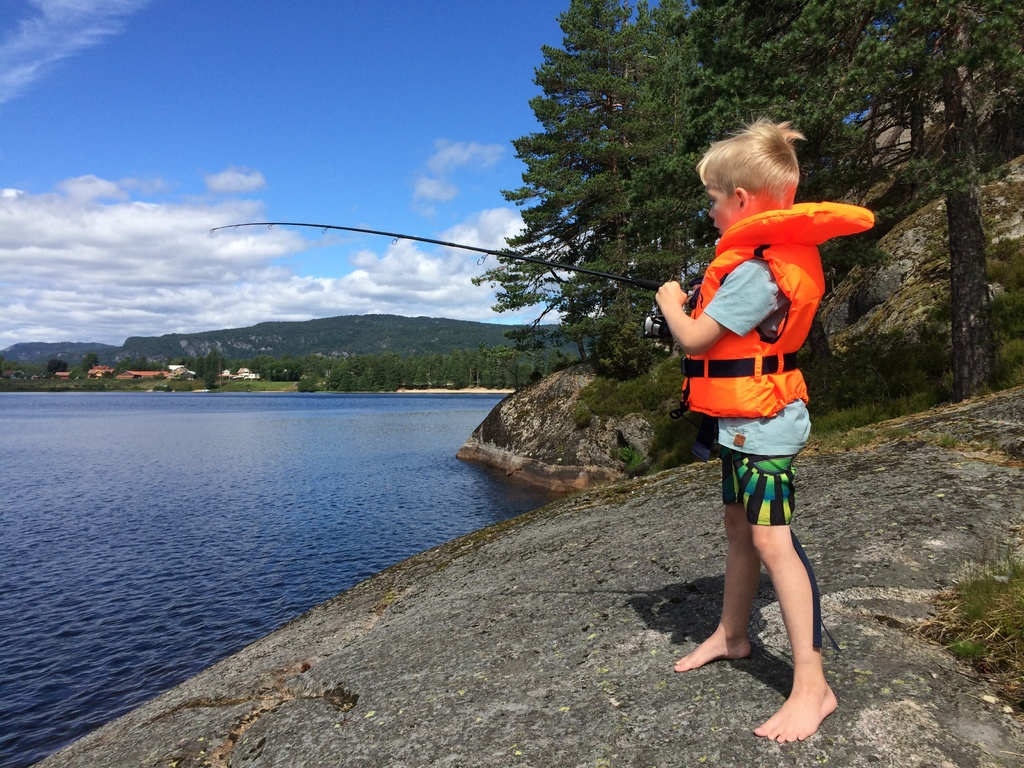 Barn med redningsvest som fisker