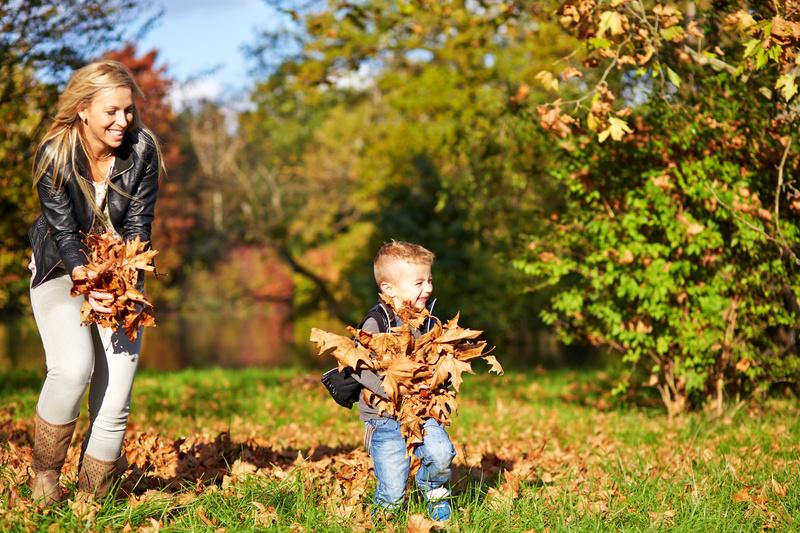 Mor og barn som leker med løv