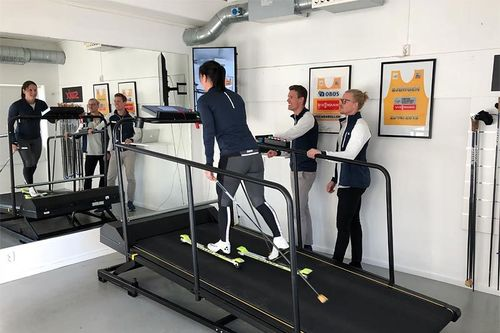 Holmenkollen Treningslab med Marit Bjørgen på treningsmølla, ringside står Ragnar Bragvin Andresen og Sondre Sundby. Foto: Holmenkollen Treningslab.