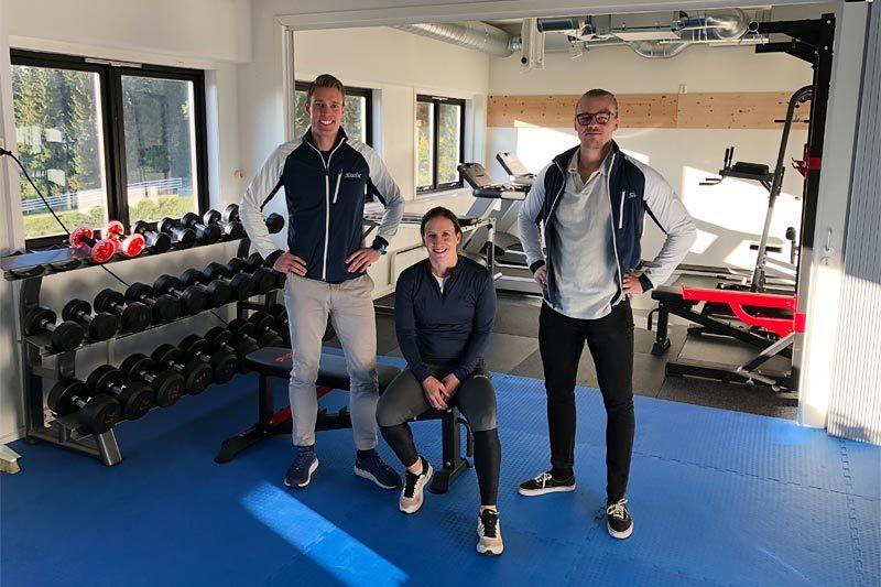 Holmenkollen Treningslab hvor Marit Bjørgen har tatt plass i treningsrommet, flankert av Ragnar Bragvin Andresen (tv) og Sondre Sundby. Foto: Holmenkollen Treningslab.