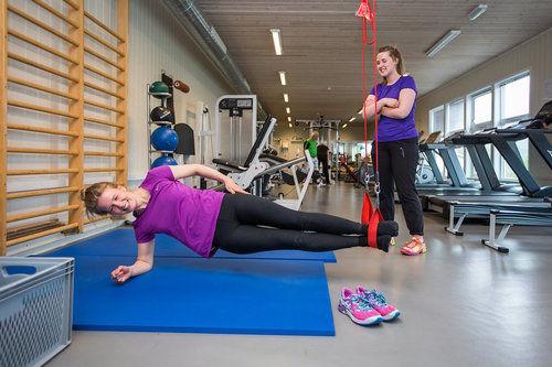 Illustrasjonsfoto fra treningssenter, 2 unge mennesker trener styrke