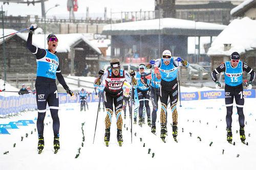 Emil Persson strekker armen i været og jubler over seier i Livigno Prologue under Visma Ski Classics sin sesongstart 2019-2020, mens Morten Eide Pedersen er nærmest i bildet og i resultatlista som nr. 2. Foto: Magnus Östh/Visma Ski Classics.