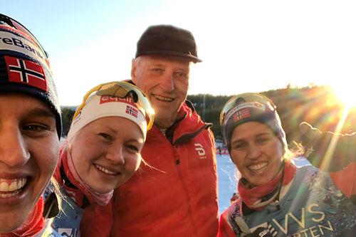 Kong Harald flankert av Amalie Håkonsen Ous, Lotta Udnes Weng og Tiril Udnes Weng etter at de hadde gått inn til NM-gull i stafett 2020 på Konnerud. Foto: Thibaut/NordicFocus.Foto: Lotta Udnes Weng.