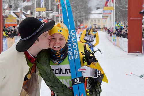 Lina Korsgren vant Vasaloppet 2020 i suveren stil og får her seierskransen og seierskysset fra den såkalte kransmasen. Foto: Schmidt / NordicFocus.