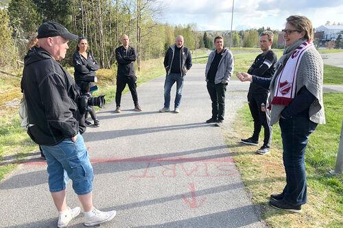 Representanter fra arrangørkomiteen, ordfører (t.h.) og journalist i lokalavisa (t.v.) i aksjon ved startsstreken under et forberedelsesmøte til Bøleråsen Rundt. Foto: Marit Haugdahl.