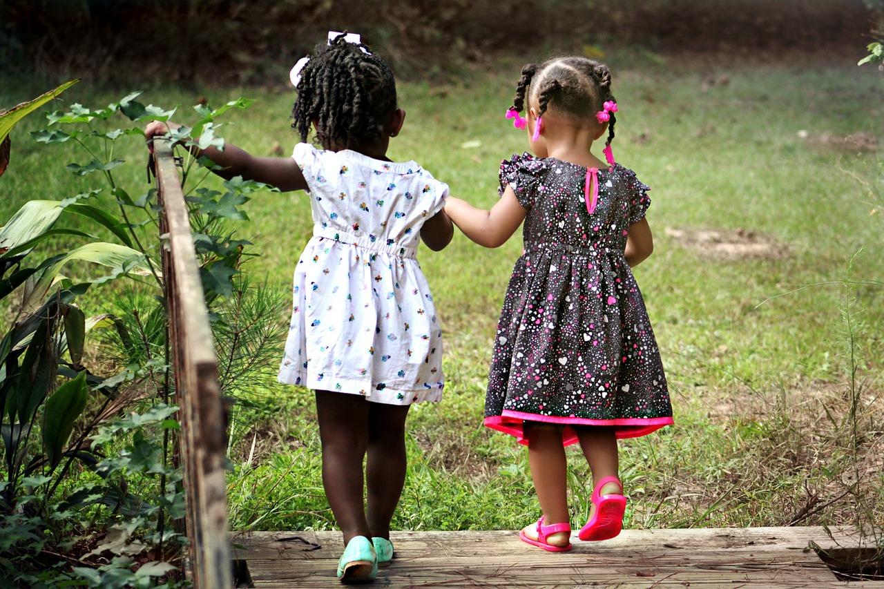 To jenter som går over en bro mens de holder hender