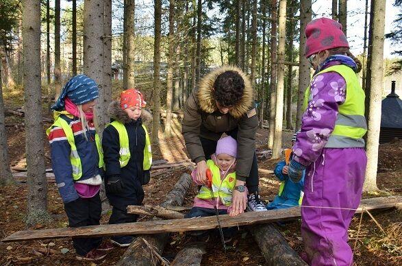 Bildet viser barn i skogen som sager.