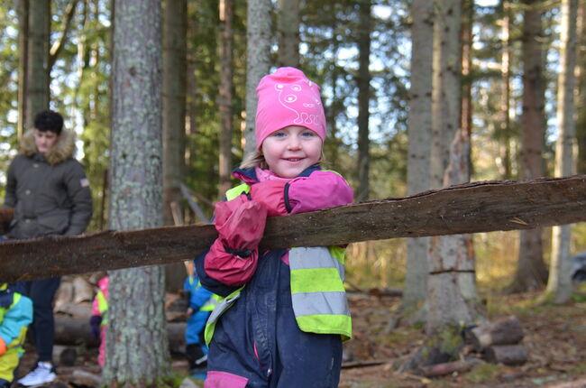 Bildet viser ei jente som leker i skogen