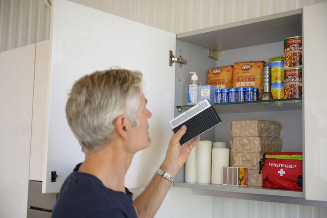 Bildet viser en som pakker et beredskapslager med mat og diverse utstyr.