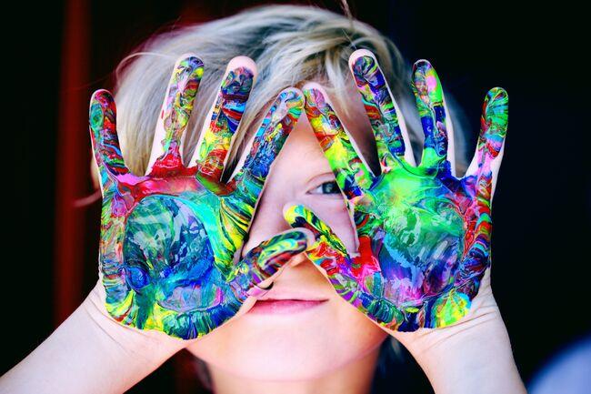 Bildet viser en gutt med maling på hendene
