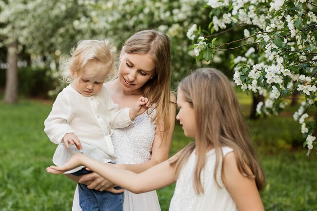 Bildet viser en voksen og to barn kledd i hvitt i en grønn hage.