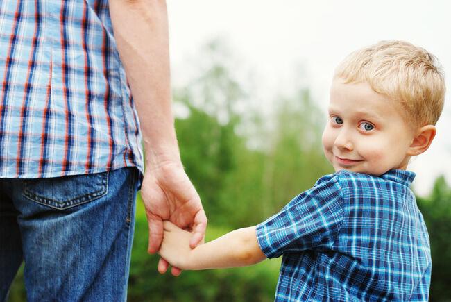Bildet viser en gutt som ser i kamera, han holder faren sin eller en voksen i hånden.