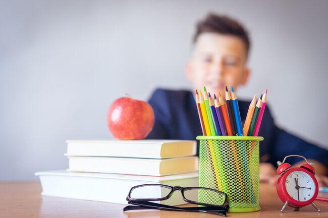 Bildet viser en elev med skolebøker på pulten