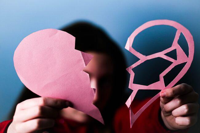 Bildet viser ei jente som holder et sønderrevet papirhjerte.