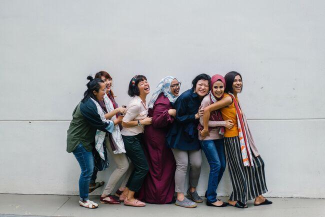 Bildet viser ulike kvinner som står på rekke og rad. De er glade og ler.
