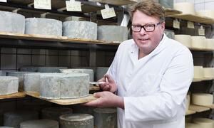 Bildet viser Olav Lie-Nilsen holder en ost i ysteriet på Thorbjørnrud hotell