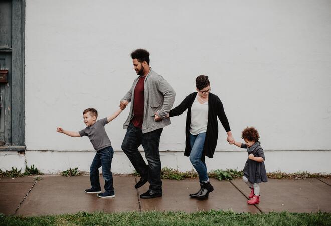 Bildet viser en familie som går på fortauet