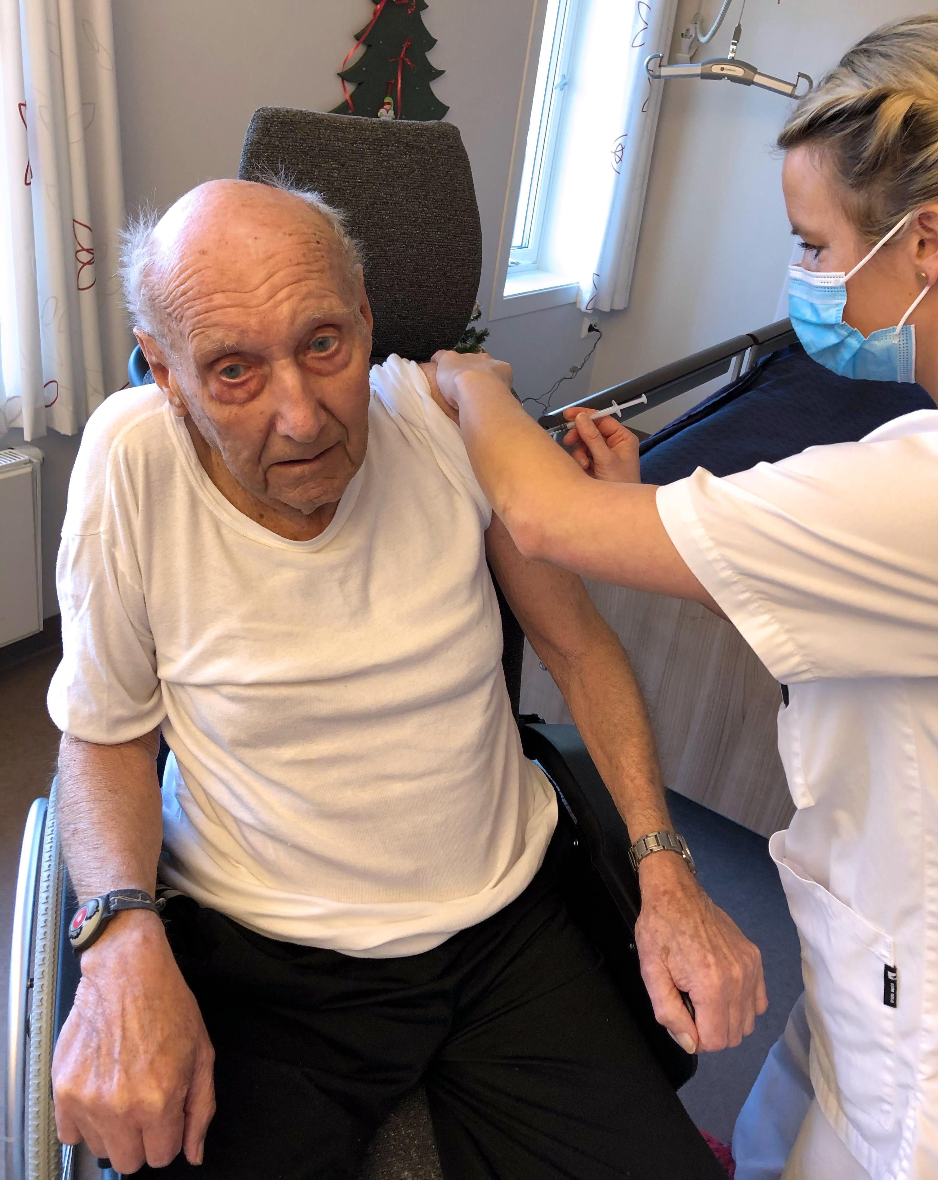 Ingolf Wiberg, på snart 86 år, var den første i Evje og Hornnes kommune til å få koronavaksine, når vaksinasjonen startet i dag, tirsdag 5. januar. Vaksinen ble satt av sykepleier Elisabeth Haugland. Bildet er gjengitt etter tillatelse fra begge.