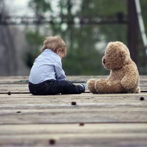 Illustrasjonsfoto. Et barn og en bamse på en vei.