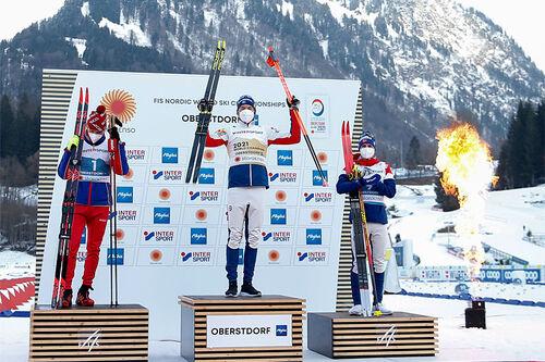 Herrenes seierspall på 5-mila under VM i Oberstdorf 2021. FV: Alexander Bolshunov (2. plass), Emil Iversen (1) og Simen Hegstad Krüger (3). Foto: Modica/NordicFocus.