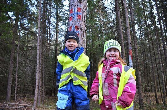 Bildet viser to barn som leker i skogen ved Bergerbakken barnehage