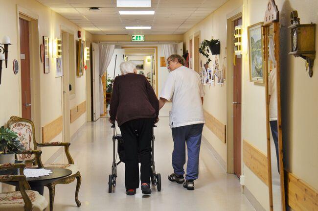 Bildet viser en ansatt og en beboer på JORS som går i korridor