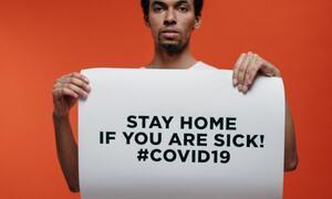 Bildet viser en mann som holder en plakat om å holde deg hjemme dersom du er syk av Covid-19.