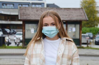 Bildet viser ei jente med munnbind