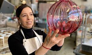 Bildet viser ei som holder opp en stor glasskuppel, lampe, blåst på Hadeland Glassverk