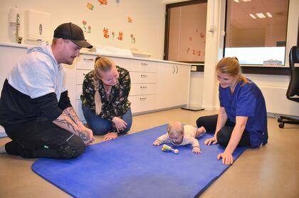 Bildet viser et barn som ligger på gulvet på en matte. Sykepleier sitter på gulvet sammen med mor og far.