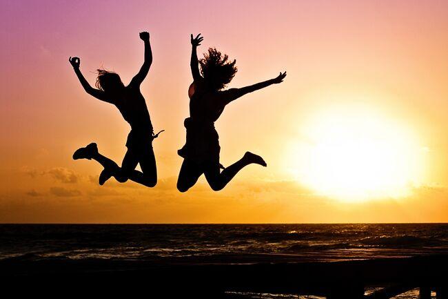 Bildet viser noen ungdommer som hopper på en strand i solnedgang
